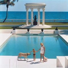 American writer C.Z. Guest (Mrs F.C. Winston Guest, 1920 - 2003) and her son Alexander Michael Douglas Dudley Guest in front of their Grecian temple pool on the