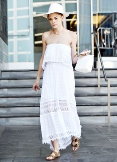 Jaime King wears a white lacey maxi dress with a white fedora, gold necklace, and leopard print sandals