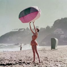 Model on the beach in swimwear photographed by Richard Rutledge for Vogue, 1952.