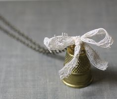 Thimble necklace vintage brass cream lace bow seamstress. $23.00, via Etsy.