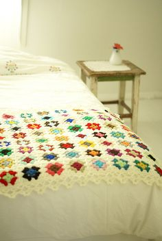 granny square afghan on white bedspread in white room. . . it works!