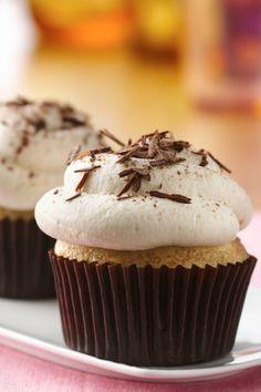Decadent tiramisu cupcakes, topped with whipped cream and chocolate shavings.