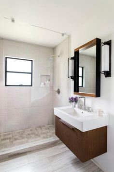 A floating vanity and spacious glass shower open up this previously cramped bathroom. Rather than splurging on stone slab counters, Brown Design Group cuts costs with a one-piece countertop and sink. A single glass-panel shower helps the room feel larger while saving on extra hardware for a swinging door. Large-format wall tiles make for a quick install.