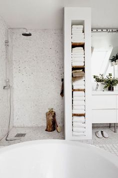 So much to love here: the crisp white tiles warmed up with touches of wood; narrow floor-to-ceiling shelves that not only store, but celebrate the linens; a deep soaking tub; deluxe rain shower head; and on and on.