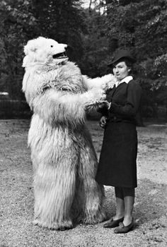 Unhappy woman dances with person in a polar bear costume, Germany, 1935.