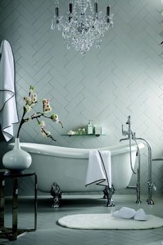 A master bathroom for my century home. Herringbone tiled wall, claw foot tub and chandelier!