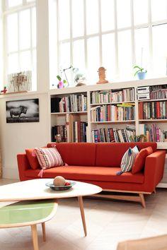 Sofá pés de madeira, estante de livros branca.
