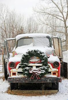 Vintage red truck with large evergreen wreath
