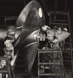 Workmen install a new propeller on the HMS Queen Mary in dry dock during an annual overhaul in Southampton.