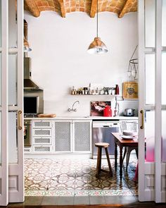 Moroccan tile floor, rustic dining set, chicken wire cabinetry with an industrial pendant