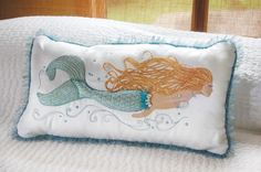 Seaside Decor Boutique    is pleased to offer the beautiful Pearl Of The Sea Mermaid Pillow .    Crafted from mixed material applique using pearly organzas, mixed tulles, metallic embroidery threads and accented with faux pearl beads. White cotton linen panels finished with fringed tulle trims and an envelope-style back panel with pearly button.    Designed filled and finished in the USA. Outer cover imported. Poly-fill.    Dimensions: 14 x 23