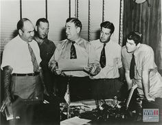 Four Higgins family members look on as Andrew Higgins holds a piece of paper in Louisiana in the 1940s. From The Digital Collections of the National WWII Museum. 2008.280.025