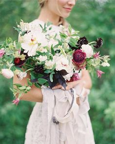 Absolutely gorgeous autumn wedding bouquet by bows and arrows flowers. Burgundy, raspberry and white with lots of tumbling, natural foliage. Features peonies, roses, ranunculus and scabious xx