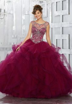 Style 89141 from Vizcaya has a jeweled sheer net bodice with cap sleeves and a keyhole back on this flounced tulle Quinceanera ball gown. Matching stole included.