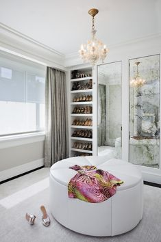 Huge white leather ottoman, fantastic shoe storage/display and antiqued mirror fronted closet doors. #closet