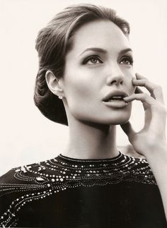 Angelina Jolie. My how she gave away her edge. Fabulous hair, earings nice, and her top is very classy in this picture.