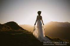 That dress! That light! We just love a mountain top wedding. Photography by Alpine Image Company