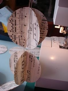 cut circles from music paper about 2.5 inches diameter. sew 2 together across diameter, then another 2, etc. dont cut them apart, when you are done you will have a ready made garland. just fold open the circles at the seam.