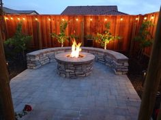 Outdoor Bar, Fire Pit, and Mini Vineyard, This is my husbands dream backyard. It includes an outdoor bar cooking area, BBQ, fire pit, mini vineyard. One day we will have patio furniture and chairs by the fire pit, but one thing at a time!, fire pit, built-in stone bench that matches ground pavers, and string lights , Yards Design