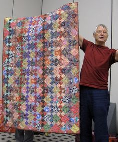 kaffe fassett liberty of london quiklt.  Interesting piecing.  The same 4-Patch block is set vertically.  The same solid block is set across the diagonal.  Like the effect this gives.