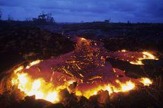 Molten lava flows across the coastal plain during the Kilauea eruption at dusk in Hawaii, Volcanoes National Park, USA.