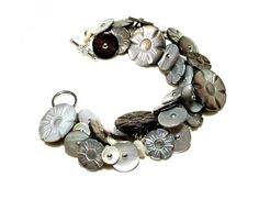 This beautiful handmade button bracelet, made by yours truly, features 48 Victorian MOP (mother of pearl) buttons. Two matching sets of buttons are carved in the shape of flowers and there are two different types of MOP shoe buttons. The MOP flower buttons date to the Victorian period and have unusual round, steel box shanks. The 4 larger MOP flower buttons measure 7/8 and the matching, smaller MOP flower buttons measure 9/16. The shoe buttons are all steel pin shank buttons and are from…