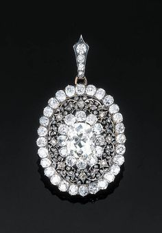 A Diamond Pendant   The central old cushion-cut diamond weighing 7.60 carats within an old-cut and rose-cut diamond floral frame, detachable diamond-set pendant hook, circa 1850, mounted in silver and gold, 6.0 cm long