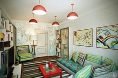 Modern White Bookcase Design With Frosted Glass Doors And Comfortable Sofa With Floral Blue Pattern Under Red Pendant Lights