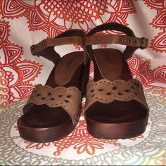 Rocky Brown Leather Heidi A pretty and dainty sandal to liven up your casual wear. Leather upper with cut-out detailing. Adjustable ankle strap. Wooden midsole and heel. Skid-proof rubber sole. 3 inch heel. Roxy Shoes Heels