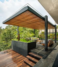 Drafting the patio with the creation of cemented deck idea with a stunning aluminum pergola on top seems fabulous together. The farther spawning of the patio is made with the placement of various wooden planters and rustic wooden furniture set to provide you the facility of relaxable seating.