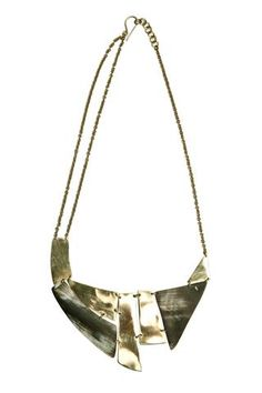 Kerina Horn + Brass Breastplate Necklace. This statement piece is made from upcycled brass and horn, ensuring that each necklace is one-of-a-kind. Handcrafted by artisans living in the Kibera slum of Nairobi, Kenya. Empowering women with an opportunity to improve their livelihoods through employment.