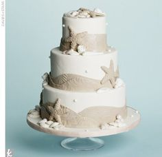 Three-tiered fondant wedding cake accented with sugar starfish, shells, and embossed fondant bands.