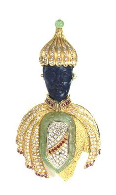A MULTI-GEM AND 18K GOLD BLACKAMOOR BROOCH, BY MESSAGLIA  1 carved emerald plaque, with typical surface reaching inclusions, 2 emerald beads, 1 carved hardstone, 34 circular-cut rubies, 280 single-cut diamonds, weighing approximately 2.00-2.50 carats total