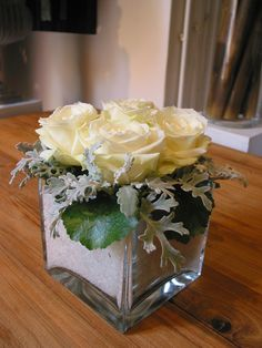 Square glass vases with salt, white roses and greenery.