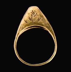 Medieval Stirrup Ring. England, 13th-14th century. Gold and sapphire. High stirrup-shaped ring set with a sapphire, the bezel engraved on both sides with a stylized flower; the rear of the bezel ajouré.
