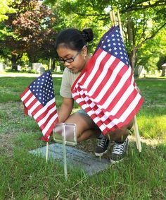 Pakthra Meas, 13, places a decorates a grave. Students from the Plouffe Academy in Brockton placed flags in Coweeset Cemetery, on Saturday, May 19, 2012. Marc Vasconcellos/The Enterprise
