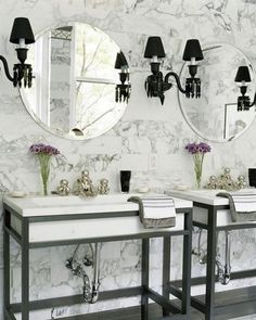 Beautiful bathroom.  The black sconces, round mirrors and the purple flowers against the marble wall make it for me.