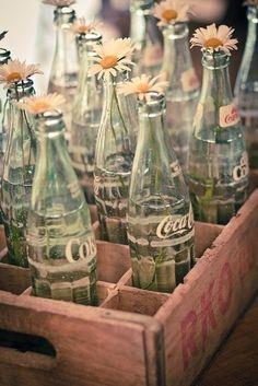 É muito comum o reaproveitamento de vidros e garrafas para decorações simples no estilo rústico. Aqui, uma inspiração perfeita para noivas da Geração Coca Cola ;)