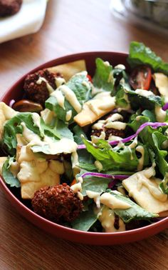 Crispy fried falafel makes eating salad fun! Try it in this falafel kale salad with tomatoes, cucumbers, pita chips, and hummus dressing – you won't be disappointed.