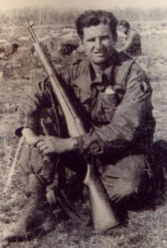 Lou Vecchi of H/506th holding the GIs best friend, the 30-06 caliber M-1 rifle designed by John Garand. Utilizing an 8 round clip, the gas-operated, semi auto weapon allowed the user to fire eight times, as fast as he could pull the trigger. This gave a distinct advantage over Axis opponents who were mostly using bolt-action rifles. photo c/o Bob Martin.