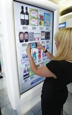 The supermarket has set up virtual fridges and cupboards around the airport to let travellers browse and buy using a smartphone app, then have th...