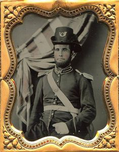 """Very nice early war ruby ambrotype of a Yankee soldier. He is wearing an interesting frock with a buff white cartridge box sling and breast plate with a matching buff white leather belt and a M1839 """"baby"""" US belt plate. He is topped off with a Hardee hat with infantry insignia pinned to the front and an ostrich plume to the side."""