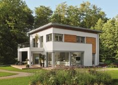 The City Life 700 Passive House has a modern design with a white exterior and some wooden elements. Flat Roof House Designs, Modern House Design, Keitel Haus, Living Haus, Model House Plan, Home Building Design, Family House Plans, Dream House Exterior, Architectural Design House Plans