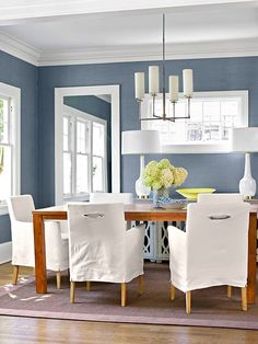 Pairing icy blue walls with plenty of white accents helps the hue come off as cool, not frigid. In this dining room, clean-lined chairs and light fixtures remain true to the simplistic mentality of the room, while wood finishes and a natural weave area. Dining Room Paint Colors, Dining Room Blue, Dining Room Walls, Dining Room Design, Colorful Dining Rooms, Dining Chairs, Lounge Chairs, Kitchen Dining, Dining Room Light Fixtures