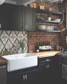 cozy kitchen with black cabinetry, exposed brick walls, butcher block countertop, and white apron sink