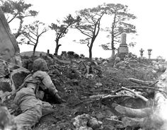 "MAY 21 1945 Okinawa – Medal of Honor for Conscientious Objector - See more at: http://ww2today.com/ Marines move through and over ""CEMETERY RIDGE."" They are shown pinned down behind gravestones by enemy sniper fire."