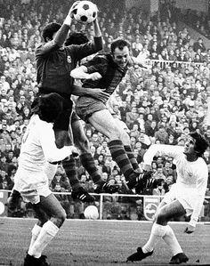 García Remón atrapa un balón aéreo ante el azulgrana Gallego. Santillana, que había bajado a ayudar en defensa, contempla la acción. Imagen de un partido de Liga de la temporada 1971-72, que acabó en tablas (1-1).