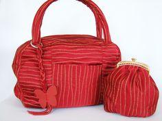 Adorazione Rosso    Durch den hocheleganter Stoff mit seiner natürlich anmutenden Linienstruktur wirkt diese Tasche ganz besonders. Sie ist eine schöne und praktische Begleiterin. Dazu passend eine kleine Bügeltasche, die auch als Kosmetiktäschchen genutzt werden kann.