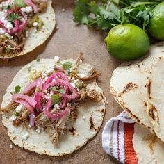 Carnitas Tacos with Pickled Onions, Salsa Verde, and Queso Fresco.
