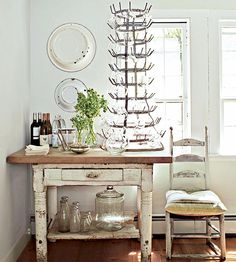 Pretty Pantry - An antique jadeite bowl inspired the color palette for the pantry. A French wine bottle holder provides a decorative spot to store glasses. The antique table not only provides storage space, but it also adds undeniable flea market character in an unexpected place.